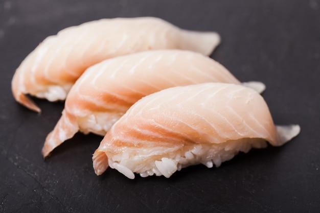 Zbliżenie tai nigiri sushi na czarnym tle łupków