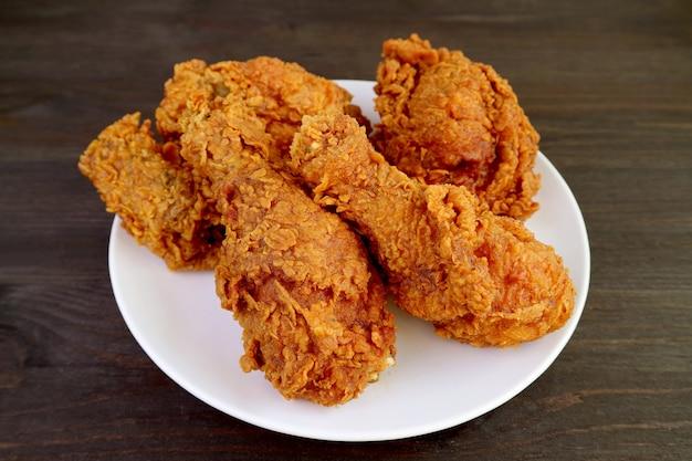Zbliżenie Talerz Przepysznych Złotobrązowych Chrupiących Smażonych Kurczaków Na Drewnianym Stole Premium Zdjęcia