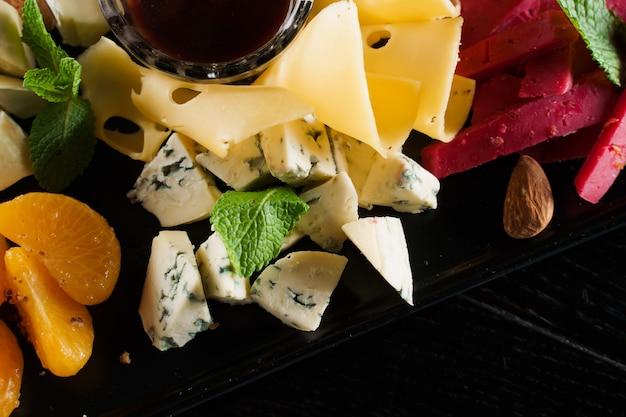 Zbliżenie talerz sera. deska z pysznym parmezanem, dorblu, serem miękkim, serem camembert. dostawa jedzenia