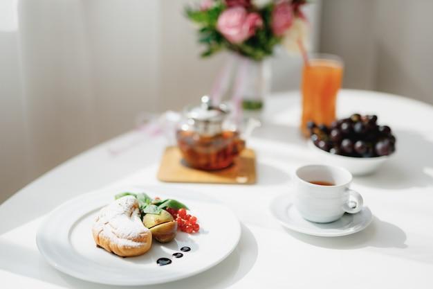 Zbliżenie talerz z rogalik pokrojone figi i gałązką czerwonych porzeczek na białym stole