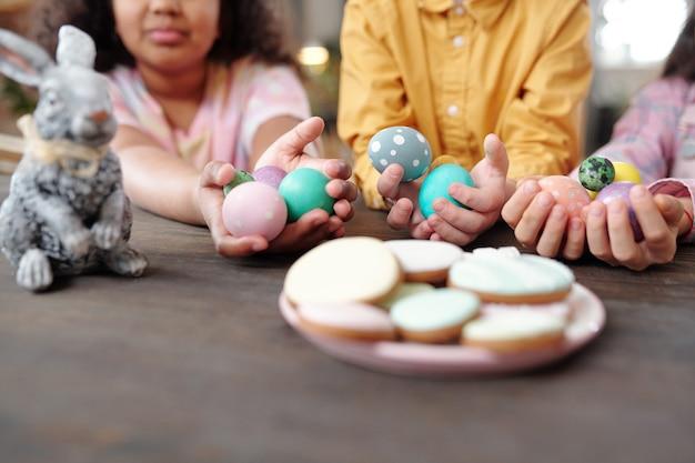 Zbliżenie talerza z domowymi ciasteczkami z grupą dzieci siedzących w tle i trzymających pisanki