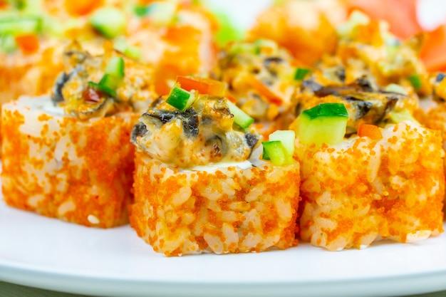 Zbliżenie talerza z sushi pokrytym czerwonym kawiorem i polewą z małży