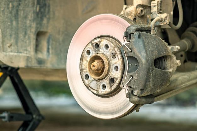 Zbliżenie tarczy hamulcowej pojazdu z zaciskiem hamulca do naprawy w trakcie wymiany nowej opony. naprawa hamulca samochodowego w garażu.