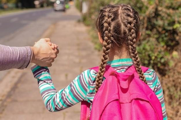 Zbliżenie tata odprowadza lub prowadzi córkę do szkoły z plecakiem lub plecakiem