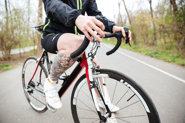 Zbliżenie tattoed młoda kobieta jedzie na rowerze w parku