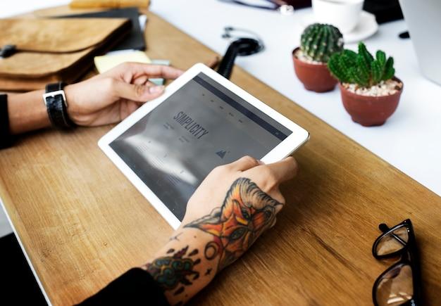 Zbliżenie tatuująca ręka trzyma cyfrową pastylkę