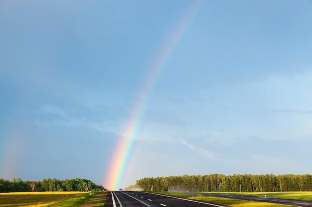 Zbliżenie tęczy w deszczu. tęczowy kolor pada bezpośrednio na mokrą autostradę