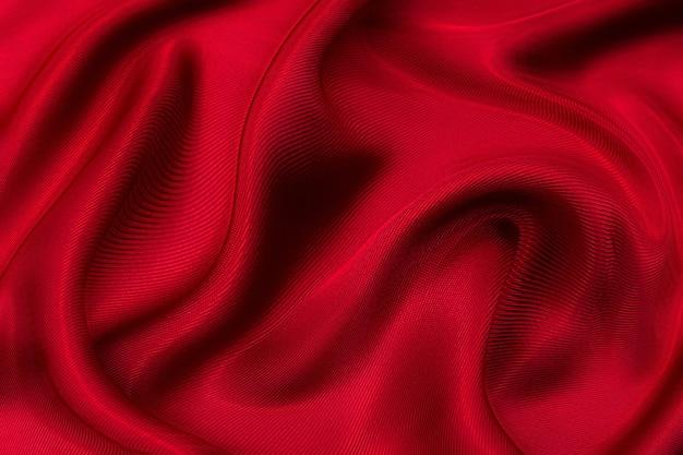 Zbliżenie tekstury naturalnej czerwonej lub różowej tkaniny lub tkaniny w tym samym kolorze. tekstura tkaniny z naturalnej bawełny, jedwabiu lub wełny lub lnianego materiału tekstylnego. czerwone i pomarańczowe płótno tło.