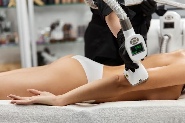 Zbliżenie: terapeuta za pomocą urządzenia lpg na ramieniu kobiety