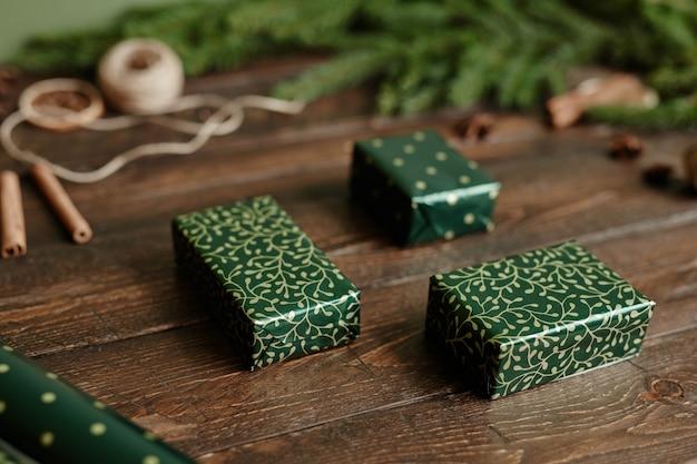 Zbliżenie tła eleganckich prezentów świątecznych zawiniętych w zielony papier na rustykalnym drewnianym stole...