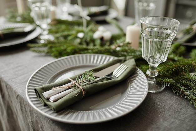 Zbliżenie tła stołu w jadalni ozdobionego na boże narodzenie gałązkami jodły i...