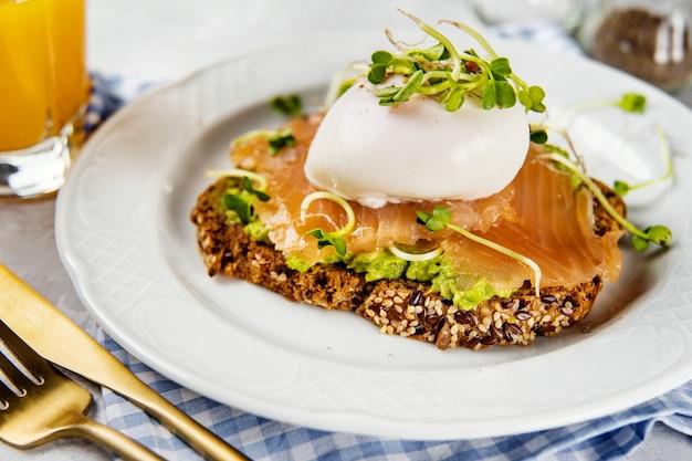 Zbliżenie toast breakfst z łososiem i jajkiem w koszulce w białej płytce