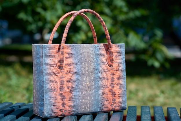 Zbliżenie: torebka modnej kobiety z imitacją skóry węża stoi na ławce w niebieskim parku. torba została wykonana w kolorach niebieskim, różowym i szarym. posiada również wygodne uchwyty.