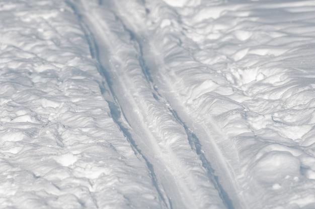 Zbliżenie toru narciarskiego na białym śniegu w zimie w jasny, słoneczny dzień.