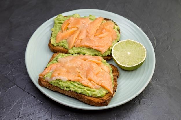 Zbliżenie tosty z ciemnego chleba żytniego, guacamole, wędzonego łososia.
