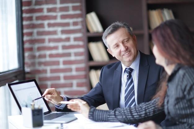 Zbliżenie.towarzysze omawiają zysk finansowy za pomocą laptopa. koncepcja partnerstwa