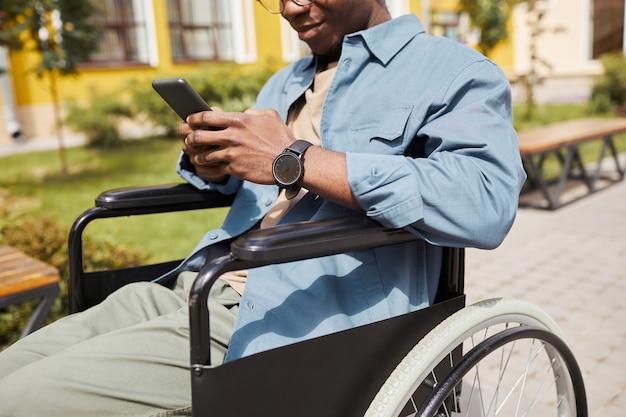 Zbliżenie treści niepełnosprawny mężczyzna w niebieskiej koszuli siedzący na wózku inwalidzkim i używający smartfona podczas czytania wiadomości w internecie na zewnątrz