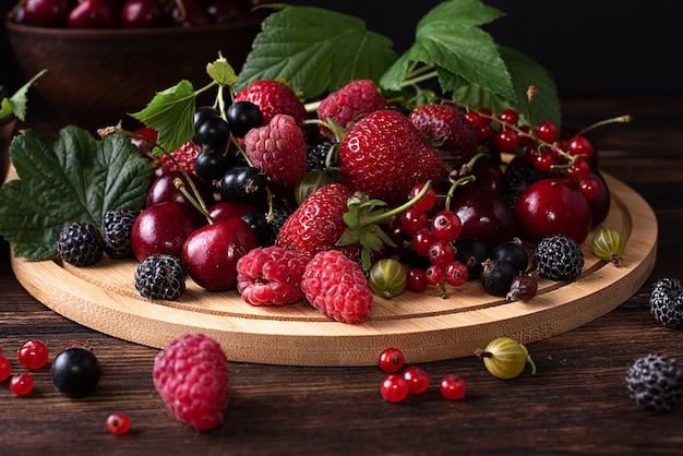 Zbliżenie: truskawki, maliny, czereśnie, porzeczki, agrest na ciemnym tle drewnianych, zdrowa żywność latem.