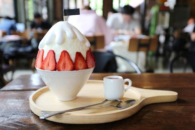 Zbliżenie truskawkowy bingzu z dojnym śniegu lodem na stole w restauraci