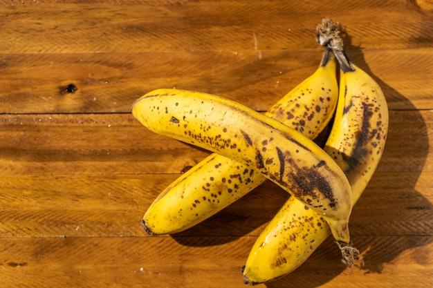 Zbliżenie trzech dojrzałych bananów na drewnianej desce. owoce tropikalne i zdrowe.