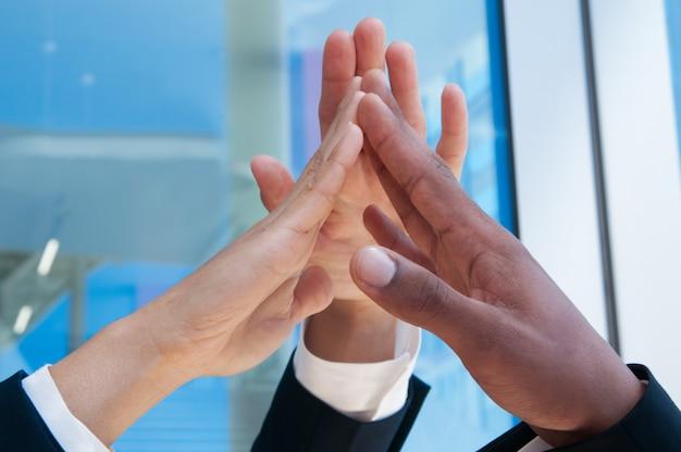 Zbliżenie trzech ludzi biznesu wysokiej fiving na zewnątrz