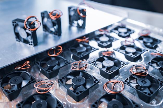Zbliżenie trzech małych chłodnic komputerowych z przewodami leżącymi na stole na szarym stole. koncepcja fabryki części komputerowych.