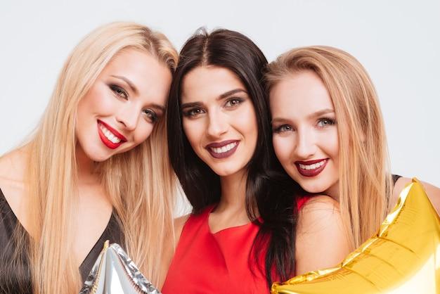 Zbliżenie trzech uśmiechniętych wspaniałych dziewczyn z jasnym makijażem na białym tle
