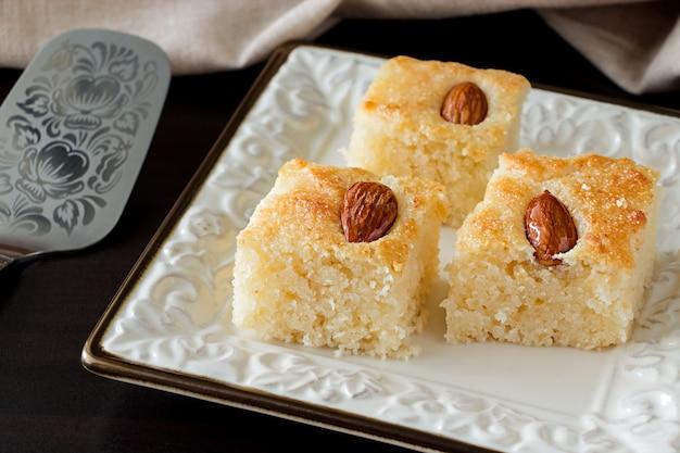 Zbliżenie trzy kawałki basbousa tradycyjny arabski tort manna z orzechami migdałowymi woda z pomarańczowym kwiatem. skopiuj miejsce. ciemne tło.