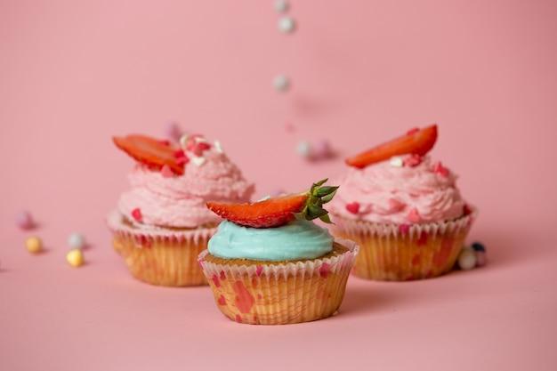 Zbliżenie trzy kolorowe babeczki z truskawkami na różowej powierzchni z kolorowymi cukierkami