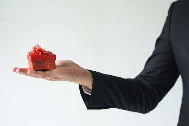 Zbliżenie trzyma małego prezenta pudełko biznesowy mężczyzna