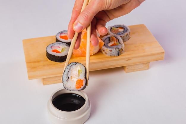 Zbliżenie: trzymając się za ręce sushi pałeczkami i zanurzając w sosie sojowym na białym tle.