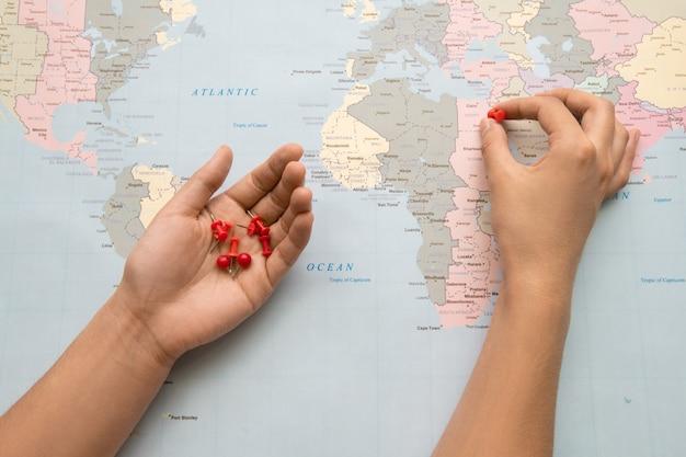 Zbliżenie turysty stawiając czerwone szpilki na papierowej mapie podczas tworzenia miejsca do odwiedzenia