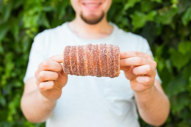 Zbliżenie turystycznych trzyma w ręku tło trdlo lub trdelnik. świeże apetyczny trdlo lub trdelnik - tradycyjne czeskie słodkie ciasto ciasta.