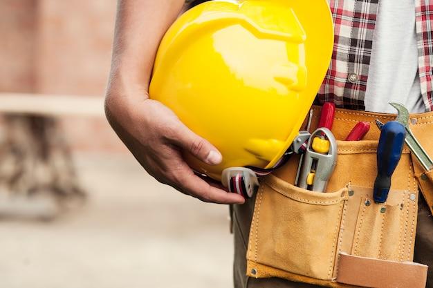 Zbliżenie: twardy kapelusz gospodarstwa przez pracownika budowlanego
