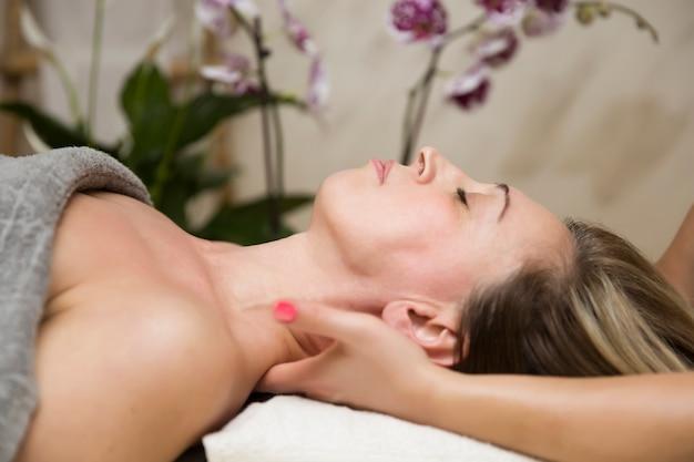 Zbliżenie twarz kobieta ma szyja masaż przy zdrojem