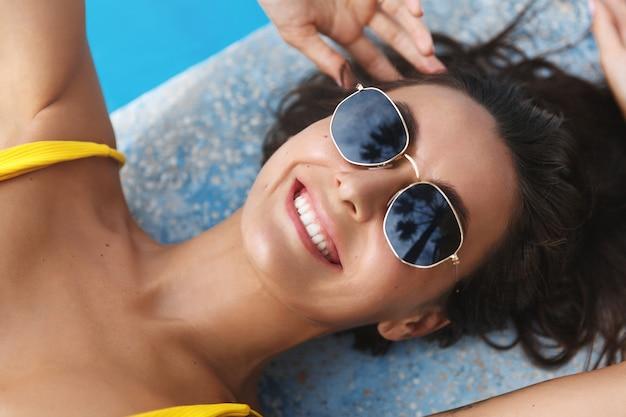 Zbliżenie twarzy atrakcyjnej kobiety w okulary przeciwsłoneczne, opalanie i leżący hotel krawędzi basenu.
