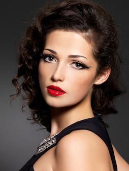 Zbliżenie twarzy brunetki kobiety z makijażem mody i czerwonymi ustami