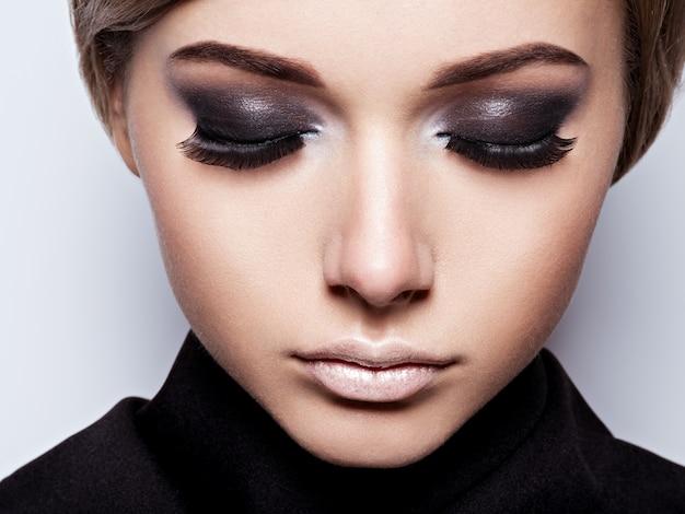 Zbliżenie twarzy dziewczyny z długimi czarnymi rzęsami. makijaż mody