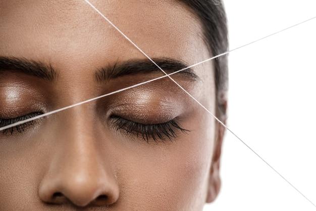 Zbliżenie twarzy kobiety indyjskiej z nitką. nitkowanie brwi - zabieg depilacji korygujący kształt brwi