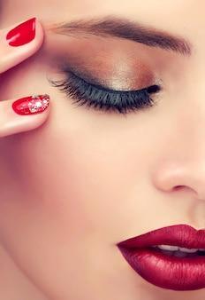 Zbliżenie twarzy kobiety ukazuje zamknięte oko zakryte powieką w przydymionym makijażu, dobrze ukształtowaną brew i jaskrawoczerwone usta. produkty do makijażu, manicure i kosmetyki.