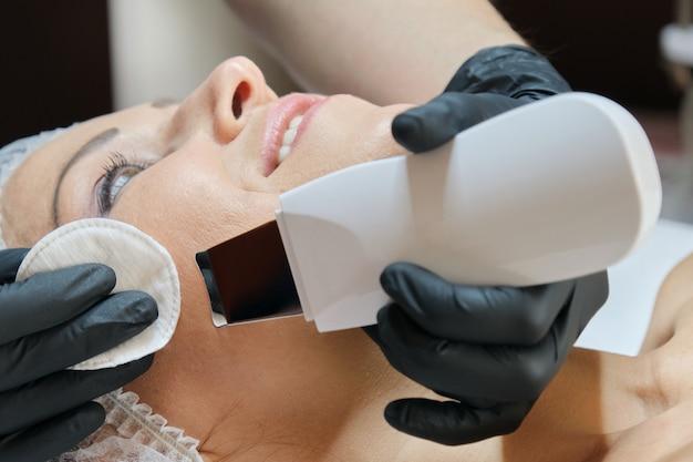 Zbliżenie twarzy kobiety w średnim wieku na zabiegi w salonie piękności