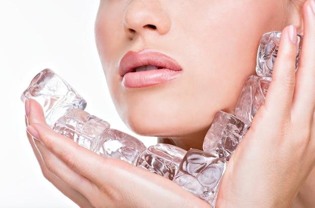 Zbliżenie twarzy kobiety z kostkami lodu wody w twarz