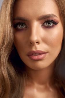 Zbliżenie twarzy kobiety z pięknym jasnym makijażem. kobieta moda ze stawianiem faliste włosy. pojęcie elegancji i piękna.