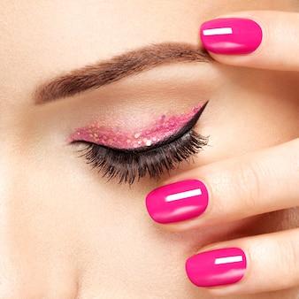 Zbliżenie twarzy kobiety z różowymi paznokciami w pobliżu oczu. paznokcie z różowym manicure