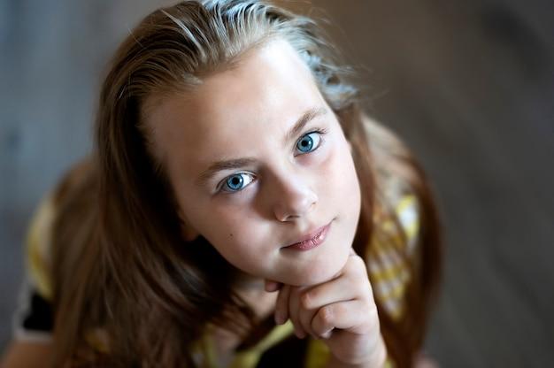 Zbliżenie twarzy ładnej nastoletniej dziewczyny z niebieskimi oczami patrzącej na kamerę