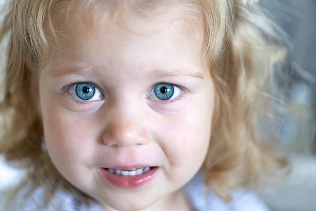 Zbliżenie twarzy małej słodkiej dziewczyny z dużymi niebieskimi oczami pełnymi smutku.