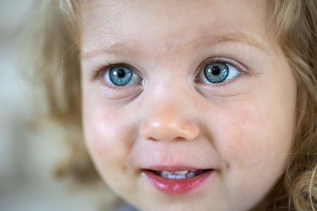 Zbliżenie twarzy małej słodkiej dziewczyny z dużymi niebieskimi oczami.