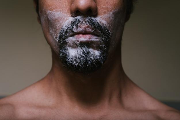 Zbliżenie twarzy młodego latynosa, który nie widzi oczu i ma piankę do golenia w brodzie z nagim torsem