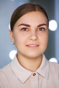 Zbliżenie twarzy młodej kobiety, która właśnie wykonała permanentny tatuaż na brwi.