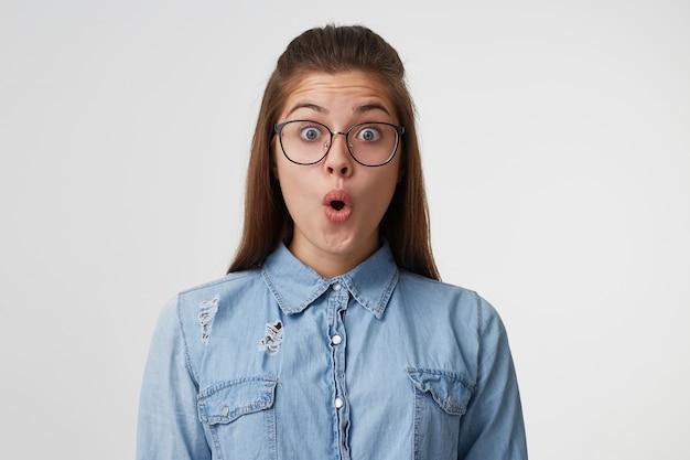 Zbliżenie twarzy młodej kobiety z długimi włosami w okularach wygląda na zaskoczonego